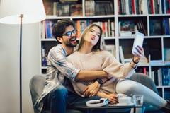 Par i inomhus kaf? genom att anv?nda den digitala minnestavlan och ha gyckel royaltyfri fotografi