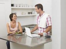 Par i kök med sallad och bärbara datorn arkivfoto