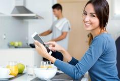 Par i köket som förbereder frukosten och bläddrar internet Fotografering för Bildbyråer
