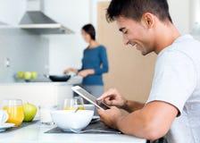 Par i köket som förbereder frukosten och bläddrar internet Arkivbild
