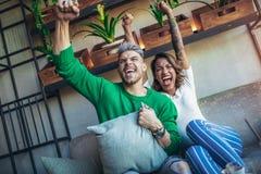 Par i kafét som ser lyckligt efter deras favorit- fotbollslag, gjorde poäng en landningsögonblick royaltyfri foto