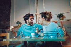 Par i kafét som ser lyckligt efter deras favorit- fotbollslag, gjorde poäng en landningsögonblick arkivbilder