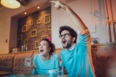 Par i kafét som ser lyckligt efter deras favorit- fotbollslag, gjorde poäng en landningsögonblick arkivfoto