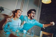 Par i kafét som ser lyckligt efter deras favorit- fotbollslag, gjorde poäng en landningsögonblick arkivfoton