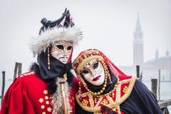 Par i röda dräkter poserar på den Venedig karnevalet Arkivfoto