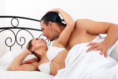 Par i säng i sovrum Fotografering för Bildbyråer