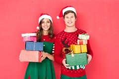 Par i santa hattar med gåvor fotografering för bildbyråer