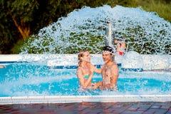 Par i swimmning pöl under den plaskande springbrunnen för sommarsun för värme varm ny termometer Royaltyfri Foto