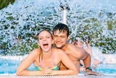 Par i swimmning pöl under den plaskande springbrunnen för sommarsun för värme varm ny termometer Arkivfoton