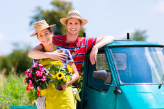 Par i trädgård med blommor gapar på Arkivfoto
