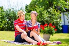 Par i trädgård på filtläseboken Arkivbild
