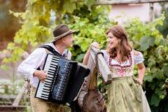 Par i traditionell bavariankläder med dragspelet, grön gar Royaltyfri Fotografi