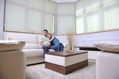 Par kopplar av hemma på sofaen i vardagsrum arkivfoton