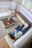 Par kopplar av hemma på sofaen i vardagsrum Royaltyfria Foton