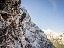 Par l'intermédiaire du grimpeur de ferrata haut sur la roche Photos stock