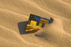 Par la carte de crédit dans le sable Photo stock