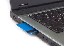 Par la carte de crédit inséré dans l'ordinateur portatif Images libres de droits