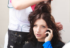 Par le styliste en coiffure. Salon de beauté parlant de coiffure de téléphone de femme d'affaires Photos stock