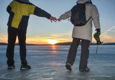 Par, man och kvinna som går på is på en djupfryst sjö fotografering för bildbyråer