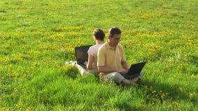Par med bärbara datorer på en äng lager videofilmer