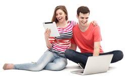 Par med bärbara datorn och den digitala minnestavlan Royaltyfria Bilder