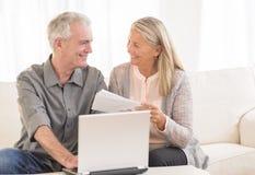 Par med bärbara datorn som betalar räkningar direktanslutet hemma arkivbild