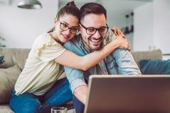 Par med bärbara datorn som tillsammans spenderar tid hemma arkivbilder