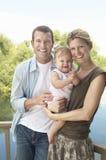 Par med barnet mot sjön Fotografering för Bildbyråer