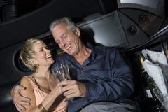 Par med Champagne Sitting In Limousine Royaltyfri Fotografi