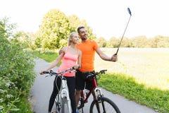 Par med cykel- och smartphoneselfiepinnen Arkivbild
