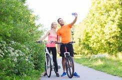 Par med cykeln som tar selfie vid smartphonen Arkivfoton