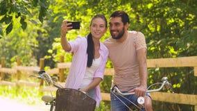 Par med cyklar som tar selfie vid smartphonen stock video