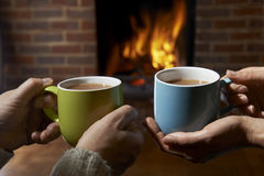 Par med den varma drinken som kopplar av vid brand Arkivbild