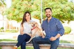 Par med deras hund på en parkera Arkivfoton
