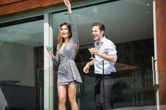 Par med drinkar som tycker om i balkong arkivfoton