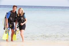 Par med dykapparatdykningutrustning som tycker om strandferie Royaltyfri Bild