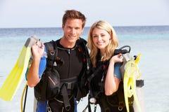 Par med dykapparatdykningutrustning som tycker om strandferie Royaltyfria Bilder