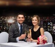 Par med exponeringsglas av champagne på restaurangen Royaltyfri Fotografi