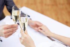 Par med exponeringsglas av champagne på restaurangen royaltyfria bilder