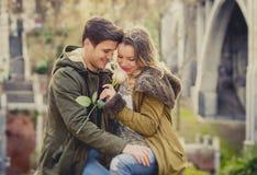 Par med förälskat kyssa för ros på gatagränden som firar valentindag med passionsammanträde på stad, parkerar Royaltyfria Bilder