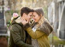 Par med förälskat kyssa för ros på gatagränden som firar valentindag med passionsammanträde på stad, parkerar Arkivbilder