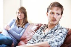 Par med förhållandesvårigheter som sitter på soffan Royaltyfria Bilder