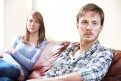 Par med förhållandesvårigheter som sitter på soffan Fotografering för Bildbyråer