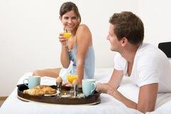 Par med frukosten i säng royaltyfria foton