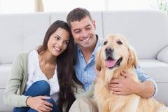 Par med golden retriever i vardagsrum Fotografering för Bildbyråer