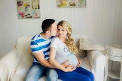 Par med gravida kvinnan som tillsammans kopplar av på soffan royaltyfri bild