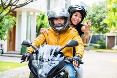 Par med hjälmar som rider motorcykeln Fotografering för Bildbyråer