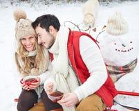 Par med hunden som dricker te i vinter royaltyfri foto