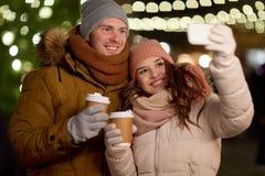 Par med kaffe som tar selfie på jul Arkivbilder