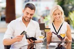 Par med kreditkortar som betalar räkningen på restaurangen Arkivbild
